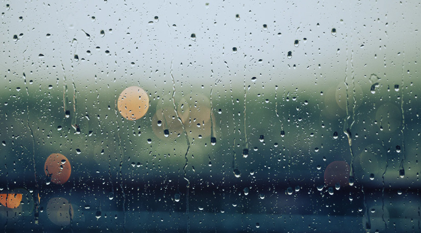 A window with rain droplets running down it