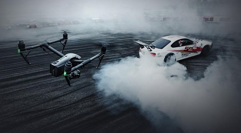 A DJI Inspire 2 drone recording over a race car