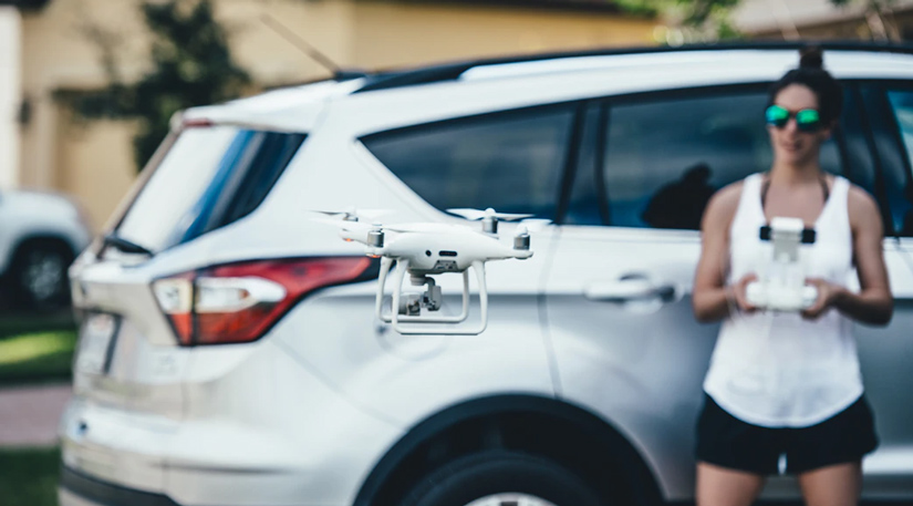 A woman flying a drone in front of her car