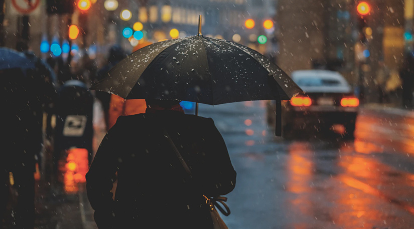 A person in a rainy street with an umbrella