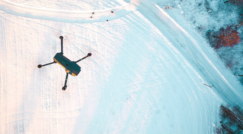 A drone flying over snow