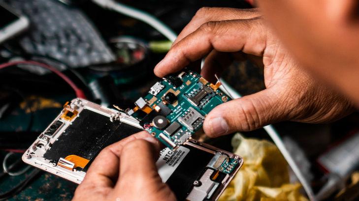 A man repairing a circuit board